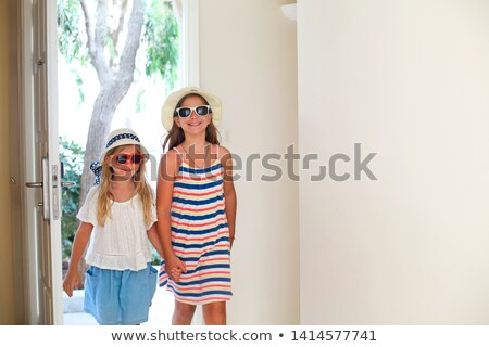Two little sisters wearing hats and glasses in hotel room  Stock photo © dashapetrenko