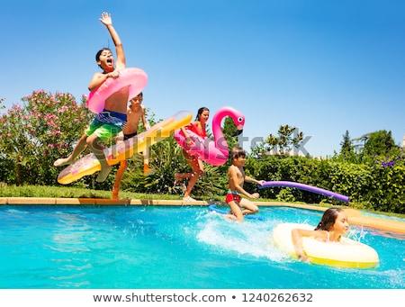 Child run jumps into outdoor pool. Happy childs for lifestyle design Stock photo © galitskaya