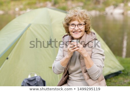 Happy mature female with hot drink looking at you while enjoying rest by tent Stock photo © pressmaster