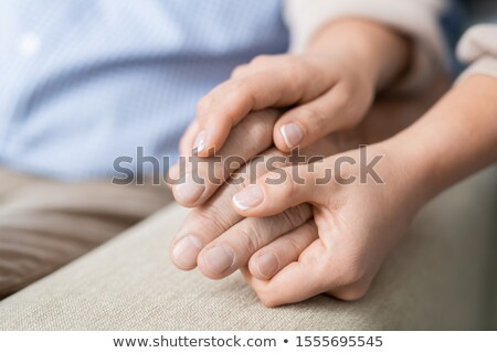 Hands of affectionate and careful daughter holding that of her senior father Stock photo © pressmaster