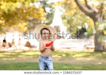 Happy child in summer in the Park in a round straw hat and shorts looking at the camera Stock photo © ElenaBatkova