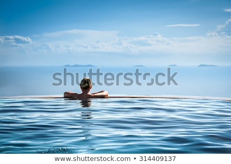 Luxury vacation woman travel tourist relaxing in infinity swimming pool on summer travel at tropical Stock photo © Maridav