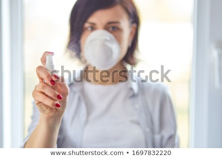 Womanl wear hygienic mask and press alcohol spray to protect, sanitizing. Stock photo © Illia