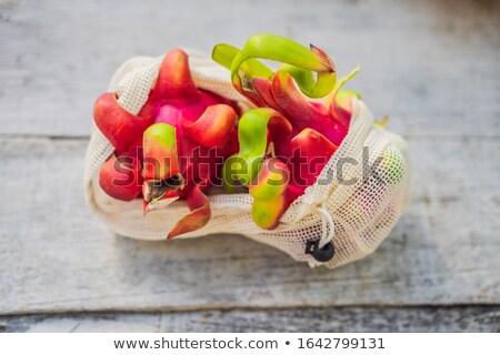 Dragon fruit in a reusable bag on a stylish wooden kitchen surface. Zero waste concept, plastic free Stock photo © galitskaya