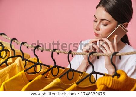 Foto Frau sprechen Handy stehen Kleiderständer Stock foto © deandrobot