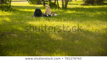 Stock photo: couple male and female with books on faces meadow