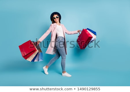 Stock photo: Photo of young joyful woman with shopping bags on the background