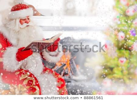 Сток-фото: Santa Sitting At The Christmas Tree Near Fireplace And Reading