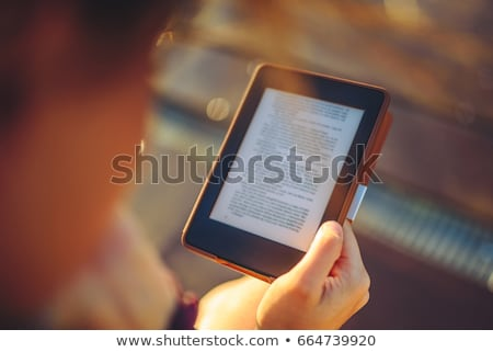 Stock photo: Woman's hands holding e-book reader