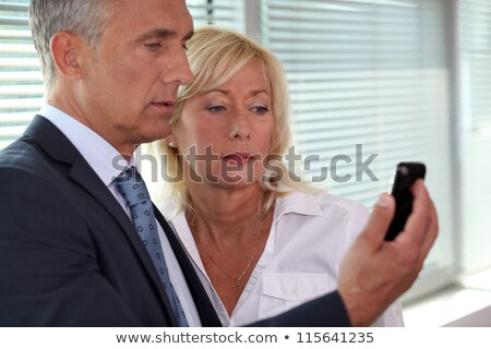 mature businessman showing his blonde wife sms Stock photo © photography33
