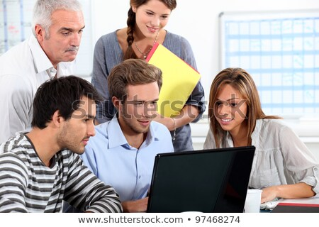Informal team of people sitting round a laptop computer Stock photo © photography33