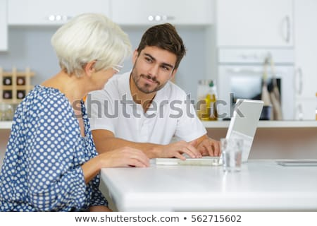 young man showing a senior woman how to use a laptop stock photo © photography33