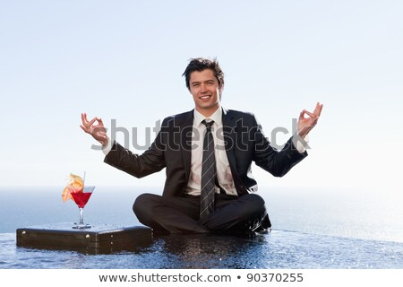 businessman relaxing in the lotus position with a cocktail in a swimming pool stock photo © wavebreak_media