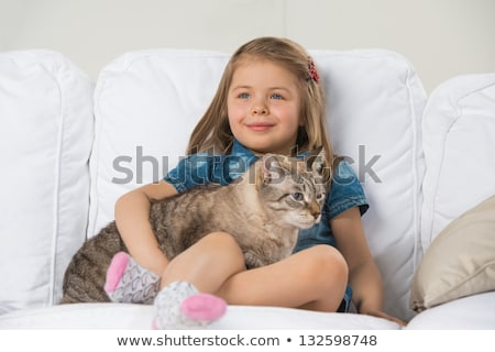 Cute little girl hugging tabby cat with love, looking away. stock photo © HASLOO