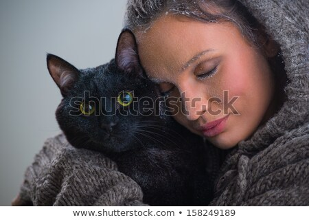 Winter portrait of young kind woman holding big black cat Stock photo © HASLOO