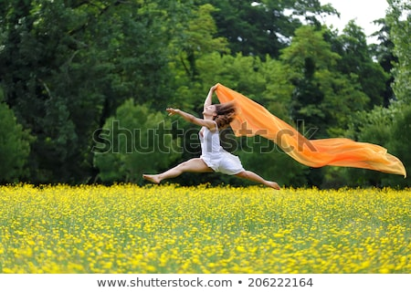 agile woman leaping in the air trailing a scarf stock photo © smithore