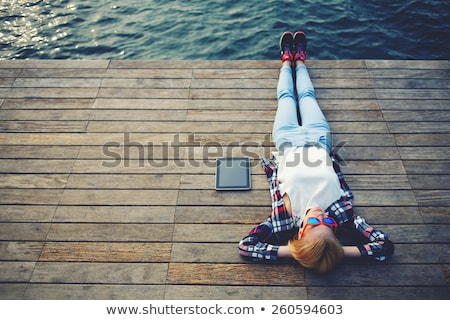 Young woman relaxing on a wooden floor Stock photo © dash