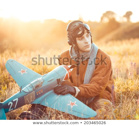 Young guy in vintage clothes pilot with an airplane model outdoo Stock photo © vlad_star