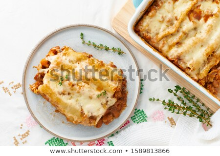 cannelloni pasta dish with tomatoe sauce on a blue plate with to Stock photo © phila54