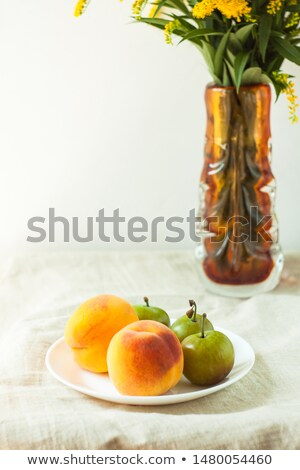 Stock photo: In front red and yellow plums on white plate