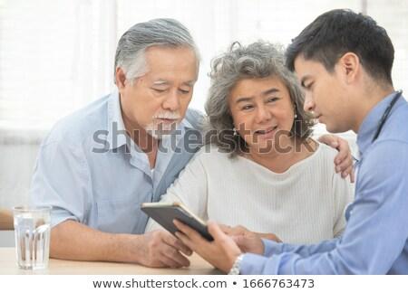 Happy couple talking to doctor Stock photo © wavebreak_media