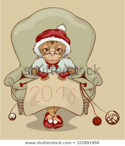 Christmas Monkey Santa is sitting in chair, knitting neckerchief 2016 Stock photo © orensila