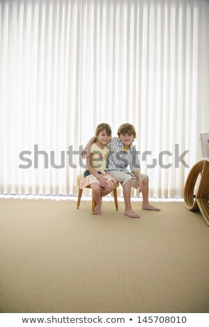 Stock photo: Mixed Race Boy Sitting on Stool in Front of Curtain