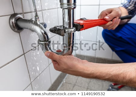 Plumber Fixing Sink Pipe In Kitchen Stock photo © AndreyPopov