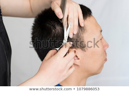 Handsome bearded man having haircut with comb and scissors  Stock photo © deandrobot