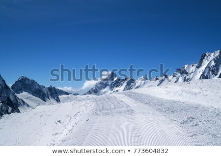 Snowy mountains at sun windy day Stock photo © BSANI
