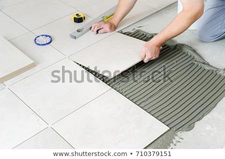 Worker tiler puts ceramic tiles  Stock photo © OleksandrO