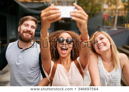 cheerful friends taking photos of themselves on smart phone stock photo © adamr