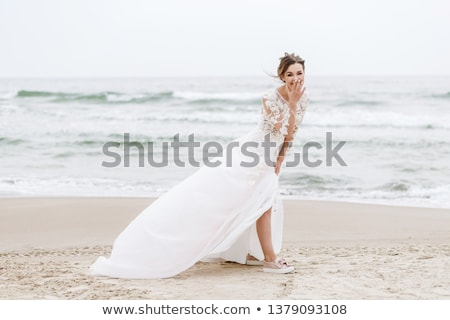 beautiful young bride in white dress standing and posing outdoors stock photo © deandrobot