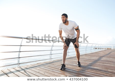Concentrated young handsome sportsman running on pier Stock photo © deandrobot