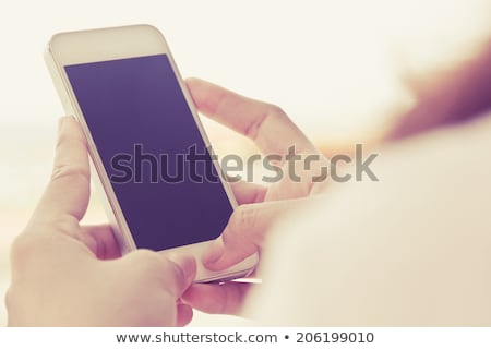 Stock photo: Close up of female hands using mobile phone outdoors
