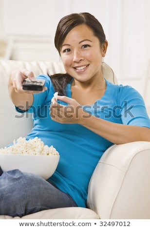 Vertical image of smiling woman sitting by table with popcorn Stock photo © deandrobot