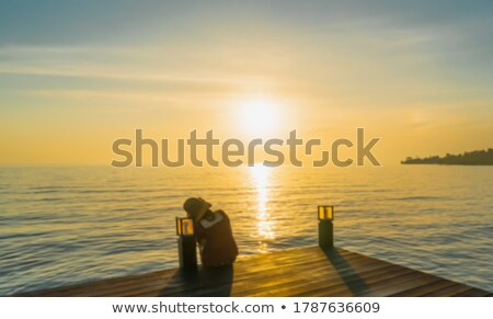 Woman sitting on the edge of balcony Stock photo © deandrobot