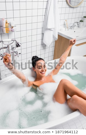 Happy attractive young woman sitting in bathtub and taking shower Stock photo © deandrobot
