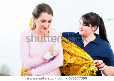 First aider helps shock victim with rescue blanket Stock photo © Kzenon