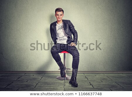 dramatic young man in leather jacket sitting and smiling Stock photo © feedough