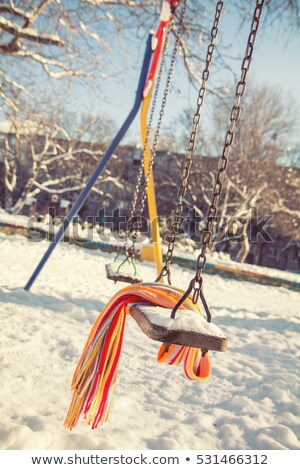 empty swing with snow and checkered scarf stock photo © artsvitlyna