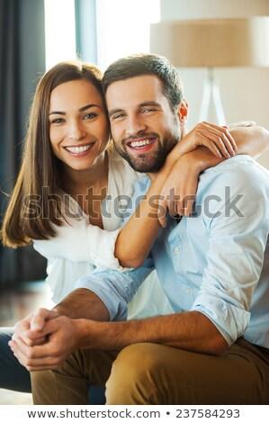 woman embracing her sitting boyfriend Stock photo © LightFieldStudios