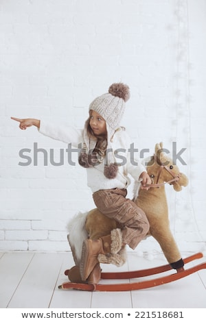little girl riding a rocking horse stock photo © is2