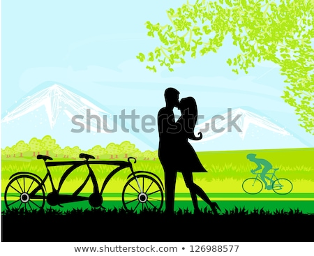 Man and woman cycling in park kissing Stock photo © IS2