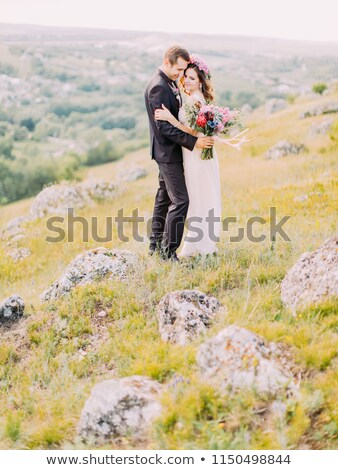 Full-length view of the hugging newlyweds standing on the mountains. Stock photo © ruslanshramko