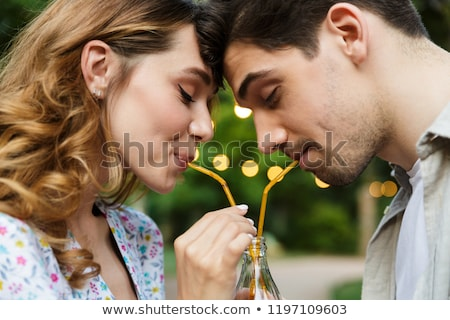 Happy young loving couple outdoors in park having fun drinking soda together. Stock photo © deandrobot