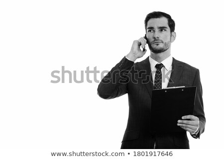 Image of handsome man 30s in business suit holding black mobile  Stock photo © deandrobot