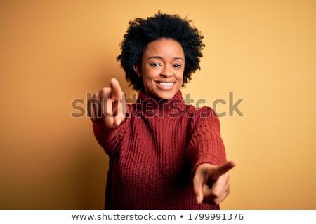 smiling young woman pointing at you stock photo © dolgachov