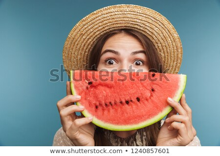 Pretty woman posing isolated over blue wall background with watermelon covering face. Stock photo © deandrobot