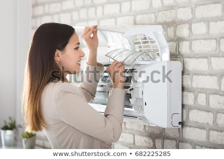 Stock photo: Businesswoman Adjusting The Temperature Of Air Conditioner